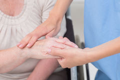 Verpleegster die flexibiliteit van patiëntenpols controleren in kliniek Stock Foto
