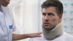 Verpleegster die gedeprimeerde mannelijke geduldige schuim cervicale kraag, halsverwondingen toepassen stock video