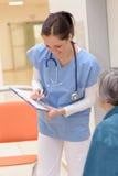 Verpleegster die geduldig dossier schrijven Royalty-vrije Stock Fotografie