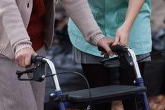 Verpleegster die gehandicapte dame met leurder helpen royalty-vrije stock afbeelding
