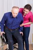 Verpleegster die gehandicapte patiënt helpen Stock Foto's