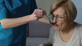 Verpleegster die gehandicapte vrouw voeden die thuis met servet, hulpeloosheid in oude dag afvegen stock videobeelden