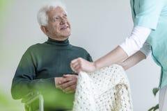 Verpleegster die gelukkig verlamd bejaarde in een rolstoel behandelen stock afbeelding