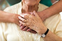 Verpleegster die haar bejaarde pati?nt troosten door haar handen te houden royalty-vrije stock foto