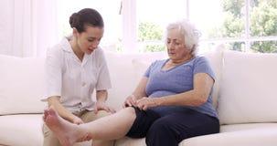 Verpleegster die het been van de hogere vrouw controleren stock footage