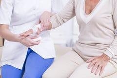 Verpleegster die het verband op woman& x27 zetten; s hand Royalty-vrije Stock Fotografie