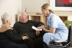 Verpleegster die hoger paar thuis bezoeken stock foto's