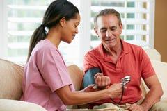 Verpleegster die Hogere Mannelijke Patiënt thuis bezoeken Stock Foto's