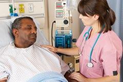 Verpleegster die Hogere Patiënt controleren op Afdeling Royalty-vrije Stock Fotografie