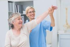 Verpleegster die hogere patiënt in het uitoefenen helpen Royalty-vrije Stock Foto