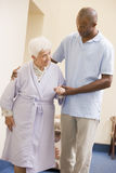 Verpleegster die Hogere Vrouw helpt te lopen Stock Foto's