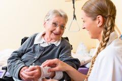 Verpleegster die hogere vrouw in pensioneringshuis behandelen Royalty-vrije Stock Afbeelding