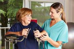 Verpleegster die hogere vrouw in rehab helpen Stock Afbeeldingen