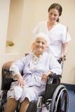 Verpleegster die Hogere Vrouw in Rolstoel duwt royalty-vrije stock fotografie
