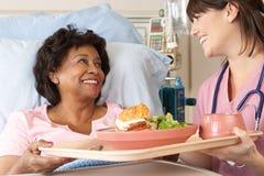 Verpleegster die Hogere Vrouwelijke Geduldige Maaltijd in het Bed van het Ziekenhuis dienen stock foto