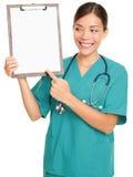 Verpleegster die klembordteken toont Royalty-vrije Stock Foto's