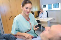 Verpleegster die mensen` s bloeddruk nemen royalty-vrije stock fotografie
