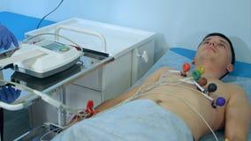 Verpleegster die met ECG-materiaal cardiogram tot test maken aan mannelijke patiënt in het ziekenhuiskliniek Stock Afbeelding