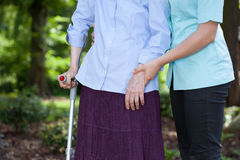 Verpleegster die met een vrouwelijke patiënt met een steunpilaar loopt Stock Fotografie