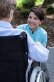 Verpleegster die met gehandicapte vrouw spreken Royalty-vrije Stock Foto's