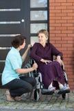 Verpleegster die met hogere vrouw op rolstoel spreken Royalty-vrije Stock Afbeelding
