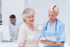 Verpleegster die met patiënt communiceren terwijl arts die computer met behulp van royalty-vrije stock foto