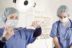 Verpleegster die met spuit in iv buis inspuit Stock Afbeeldingen