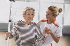 Verpleegster die naast een patiënt met IV druppel lopen Stock Afbeeldingen