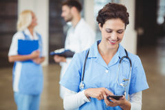Verpleegster die op mobiele telefoon gebruiken Stock Foto's