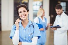Verpleegster die op mobiele telefoon spreken Stock Afbeelding