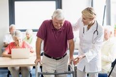 Verpleegster die oudste met het lopen hulp helpen Royalty-vrije Stock Foto