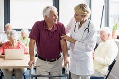 Verpleegster die oudste met het lopen hulp helpen Royalty-vrije Stock Afbeeldingen