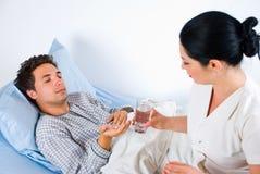 Verpleegster die pillen geeft aan een mannelijke patiënt Stock Afbeeldingen