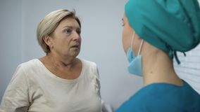 Verpleegster die rijp geduldig stuitend nieuws, angst aangejaagde vrouw vertellen die hysterically schreeuwen stock video