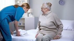 Verpleegster die schoon beddegoed voorbereiden aan bejaarde vrouwelijke pati?nt in medisch centrum stock foto