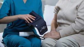 Verpleegster die verouderde vrouwelijke geduldige bloeddruk in verpleeghuis, gezondheidszorg voor bejaarden meten stock video