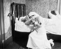 Verpleegster die voor een balling bidden die in bed liggen (Alle afgeschilderde personen leven niet langer en geen landgoed besta Stock Afbeelding
