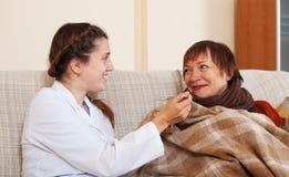 Verpleegster die voor onwel rijpe vrouw geven Stock Foto