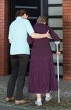 Verpleegster die vrouw het lopen met steunpilaren bevorderen Stock Foto