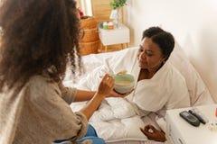 Verpleegster die wat havermoutpap voor vrouw geven die in bed na chirurgie liggen stock foto