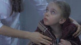 Verpleegster die weinig droevig meisje omvatten met warme plaid, kind ontbrekend huis in het ziekenhuis stock videobeelden