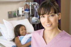 Verpleegster die zich in de Zaal van het Ziekenhuis bevindt stock afbeeldingen
