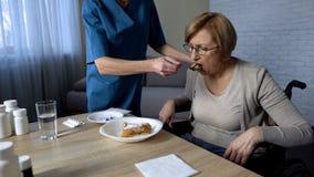 Verpleegster die ziek oud wijfje te eten, medische steun en zorg, droefheid helpen royalty-vrije stock afbeeldingen