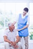 Verpleegster die zieke bejaarde patiënt behandelen Royalty-vrije Stock Foto's