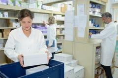 Verpleegster en apothekers die in apotheek werken stock foto's