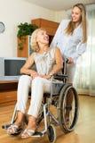 Verpleegster en gehandicapte vrouw op stoel royalty-vrije stock fotografie