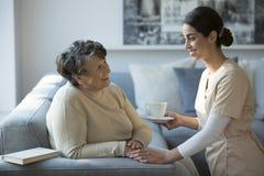 Verpleegster en glimlachende grootmoeder stock fotografie