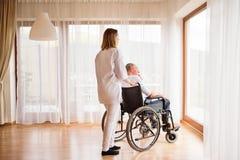 Verpleegster en hogere mens in rolstoel tijdens huisbezoek stock foto