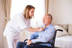 Verpleegster en hogere mens in rolstoel tijdens huisbezoek royalty-vrije stock foto's