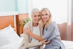 verpleegster en hogere patiënt die bij camera glimlachen terwijl samen het zitten stock fotografie